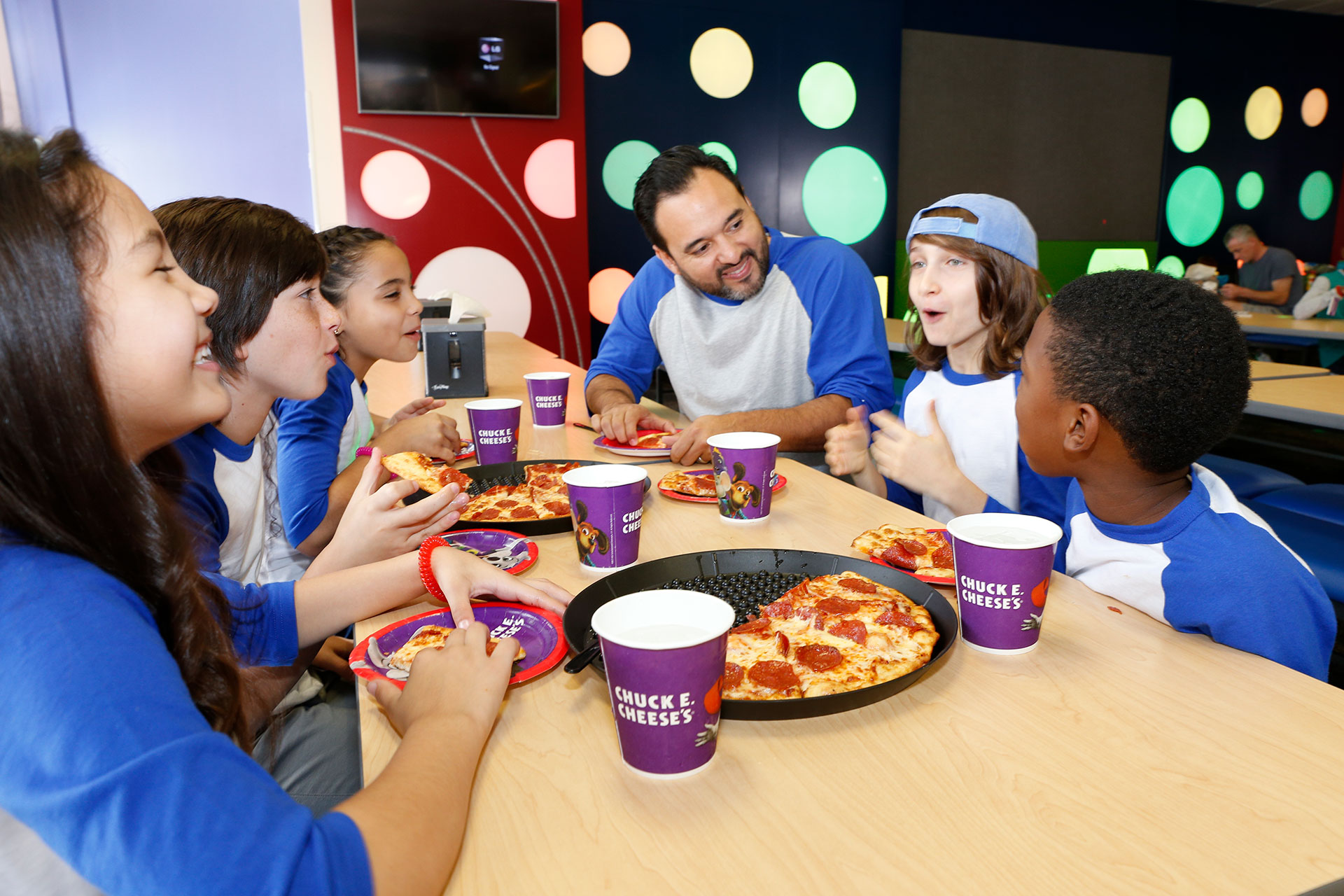 Kids team at table eating pizza