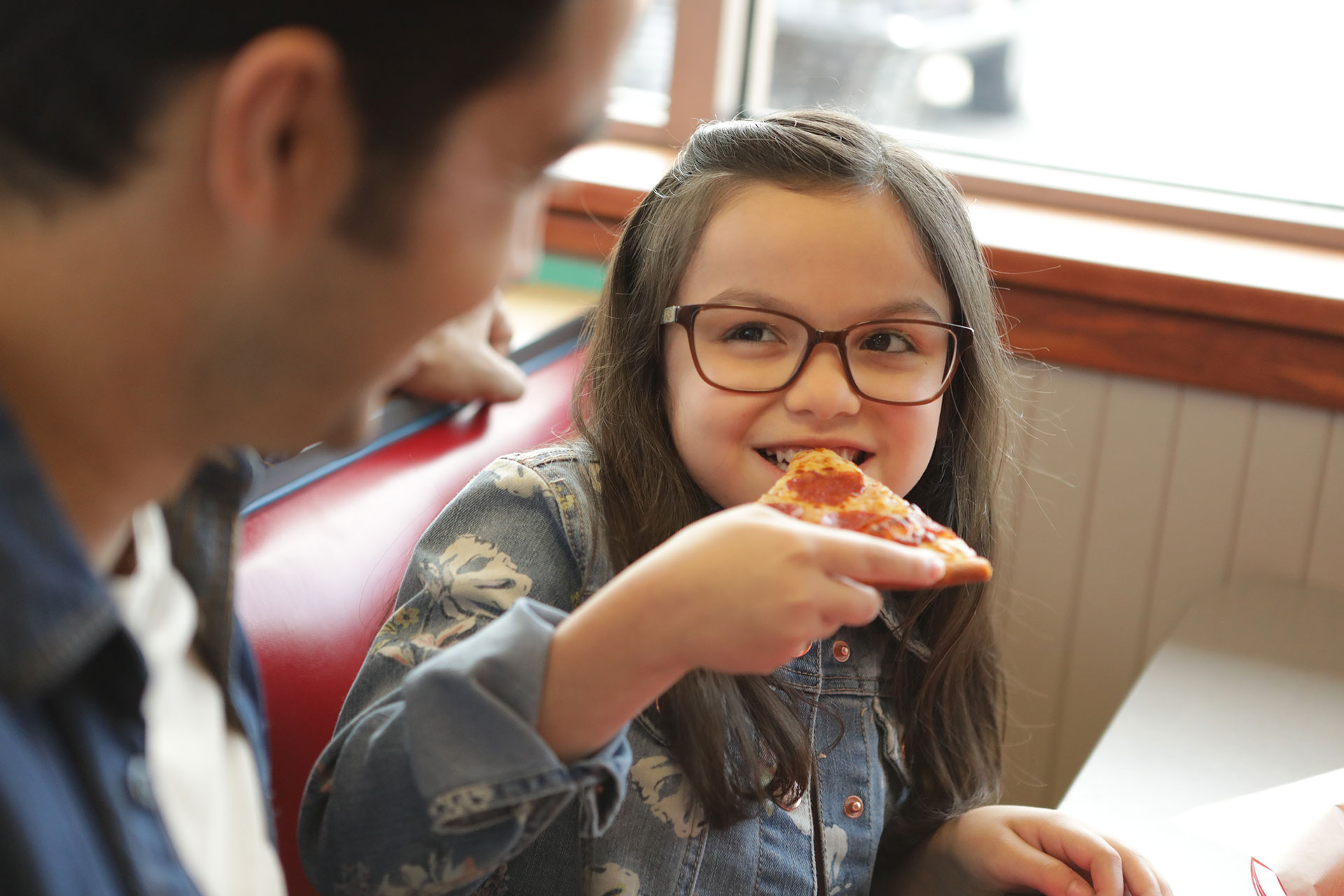Girl smiling while eating pizza